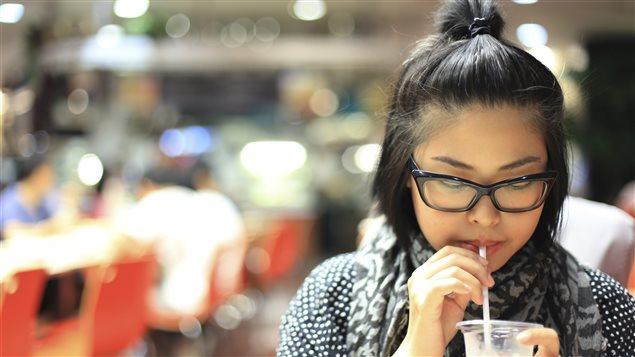 Une fille boit un breuvage dans un centre commercial.