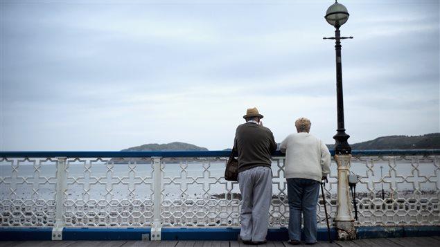 Des aînés marchent le long d'un quai.