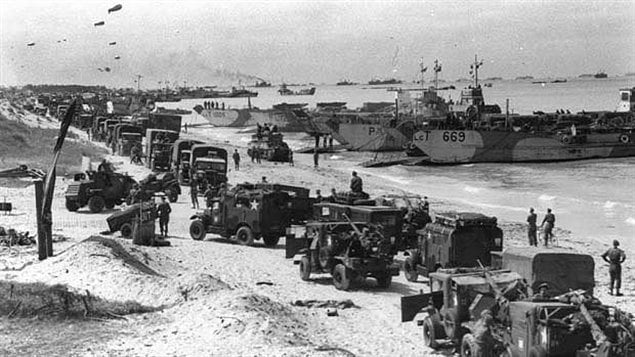 A Canadian-built Otter armoured reconnaissance vehicle turns inland from the beach ahead of a long column of Canadian CMP trucks as man and materiel gather on Juno beach just hours after the first waves came ashore. Months of bitter fighting would follow before the final German unconditional surrender.