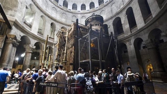 Des touristes font la queue pour visiter la tombe de Jésus à l'intérieur de l'église du Saint-Sépulcre, à Jérusalem.