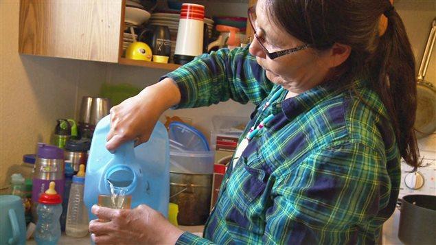 Maggie Sakanee, membre de la Première Nation Neskantaga, se verse un verre d'eau.
