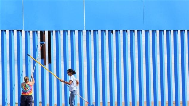 Brooke Collins et Ana Lucia Lopez peignent le mur qui sépare le Mexique des États-Unis dans la ville de Mexicali dans le cadre d'un projet aristique visant à abolir les frontières. 9 avril 2016.