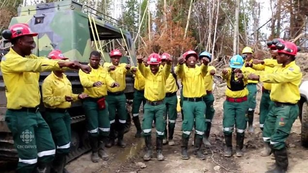 South African firefighters arrived to fight the Fort McMurray fire in the highest of spirits but are now leaving because of a wage dispute. Alberta Premier Rachel Notley is resolved to solve the problem. We see about a dozen black South African men in the Alberta bush next to a dark anti-fire vehicle on tractor treads. The men are wearing bright yellow shits, dark grey pants and hard hats. Their arms are raised in dance. Smiles crease many of their faces.