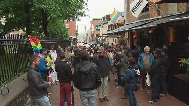 Un petit groupe de personnes devant le bar Le drague à Québec, en soutien pour les victimes d'Orlando.