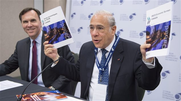 Angel Gurria, secretary-general of the Organisation for Economic Co-operation and Development (OECD) holds up copies of the results of an economic surveyor Canada as Finance Minister Bill Morneau looks on at the Conference de Montreal, Monday, June 13, 2016 in Montreal.