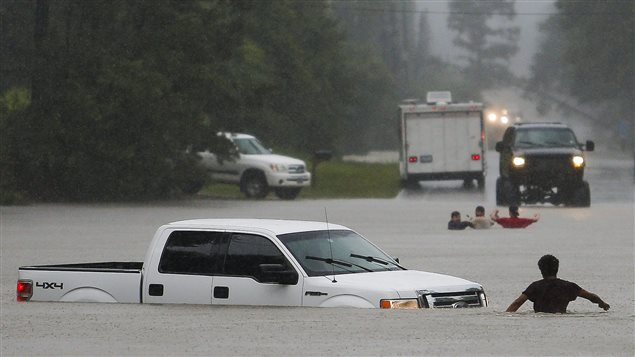 A man checks to make sure everyone made it out of a truck on May 27, 2016 in Magnolia, Texas. Intense storms and rainfall caused record flooding in the southern U.S. and parts of Europe.