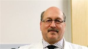 Dr. Mark Freedman, a neurologist, is the director of MS research at The Ottawa Hospital and a professor at the University of Ottawa. We see a large, balding man wearing glasses from the bottom of his chest up. He wears a dark tie under his white lab coat. He projects the air of a friendly person.