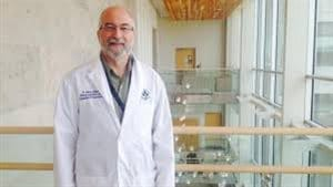 Dr. Harold Atkins is a stem cell transplant physician and scientist at The Ottawa Hospital and an associate professor at the University of Ottawa. We see a man standing with the top of an atrium behind him. He wears glasses and a lab coat and is smiling a friendly smile. He is greying and beginning to lose his hair.