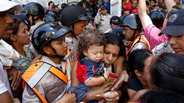 Une femme portant un enfant et de la nourriture � l'ext�rieur d'un supermarch� � Caracas. La tension monte au Venezuela contre les p�nuries alimentaires chroniques.