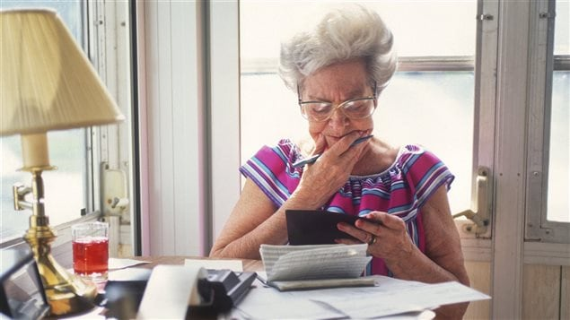 Une personne âgée analyse son carnet d'épargne