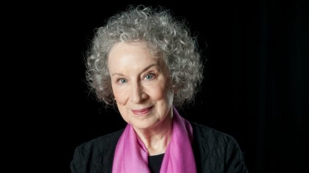 Margaret Atwood will tour the UK in the fall to promote her latest book, Hag-Seed, a re-telling of Shakespeare's 'The Tempest.' We see a lovely woman with grey, curly hair from the chest up. She wears a dark jacket, a pink scarf. A tight smile creases her lips
