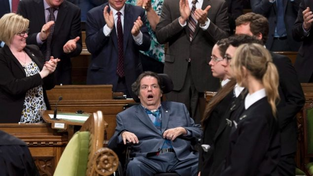 Mauril Belanger receives a standing ovation during a vote on his private member's bill to make the national anthem more gender neutral in the House of Commons on Wednesday. We see Belanger dressed in a blue suit laying back in his wheelchair, his mouth agape, his eyes wide. He is surrounded by fellow MPs and pages. The MPs are applauding. The pages stand at attention.