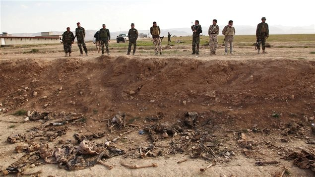 Kurdish peshmerga forces look at bones in a mass grave on the outskirts of the town of Sinjar, February 3, 2015.