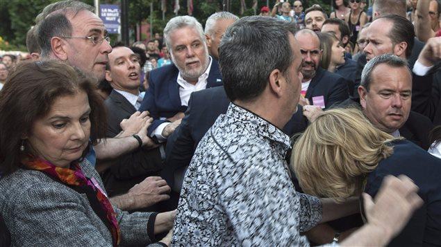 Le premier ministre Couillard est forcé de quitter la rue Sainte-Catherine où un individu l'a agressé.