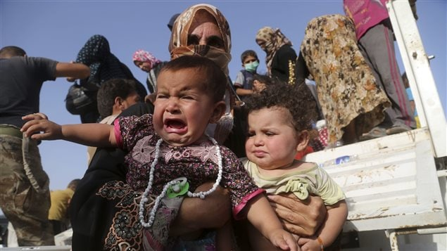 In this June 3, 2016 photo Iraqi families flee fighting near Fallujah. The UN says over 65 million people fled their homes in 2016.
