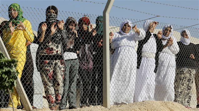 Yazidi refugee women stand behind fences as they wait for the arrival of United Nations High Commissioner for Refugees Special Envoy Angelina Jolie at a Syrian and Iraqi refugee camp in the southern Turkish town of Midyat in Mardin province, Turkey, June 20, 2015.