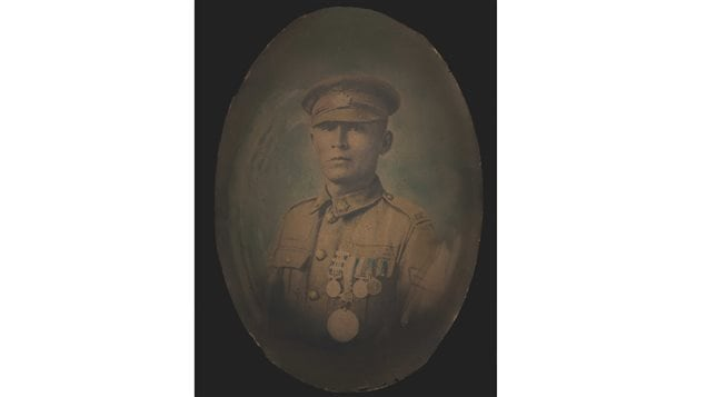 A painted photograph of Corporal Francis Pegahmagabow dressed in his military uniform and wearing his medals. Originally a black and white photo, the portrait has been coloured with oil paints. Pegahmagabow, a sniper and scout, was awarded three Military Medals.