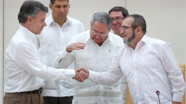 El presidente de Cuba, Raúl Castro (centro) reacciona mientras el presidente de Colombia, Juan Manuel Santos (izquierda) y el líder rebelde de las FARC Rodrigo Londoño, más conocido como Timochenko, se dan la mano en La Habana.