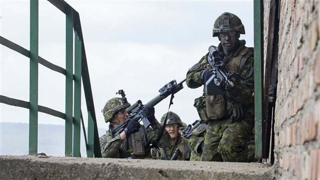 Sergeant Marco Tremblay, Corporal Benoit Seguin-Perron and Corporal Jean-Guillaume Bibeau, members from 1st Battalion, Royal 22e Régiment, advance toward a building during a joint training scenario organized as part of Exercise ANAKONDA in Wedrzyn, Poland on June 14, 2016.