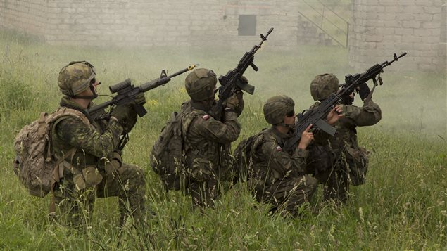 Sgt. Frederik Essiambre (left), an engineer of 5 Combat Engineer Regiment deployed to Poland as part of the Operation REASSURANCE Land Task Force (LTF), participates in an urban assault alongside a Polish Army section during Exercise ANAKONDA, in Wedrzyn, Poland on June 9, 2016.