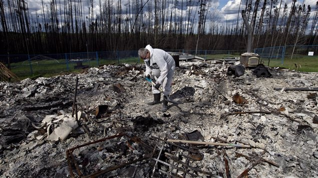 Wade Wilson digs for possessions after fire destroyed his home near Fort McMurray in the western province of Alberta.