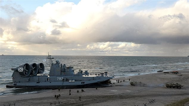 A picture taken on September 26, 2013, shows a Russian Navy Zubr class hovercraft unloading armoured personnel carriers on the seashore during a joint military exercises of Russian and Belarus troops at the Khmelevka firing range in the Russia's enclave of Kaliningrad.