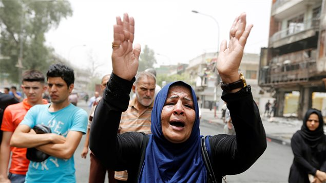 A woman reacts at the site after a suicide car bomb attack at the shopping area of Karrada, a largely Shi'ite district, in Baghdad, Iraq July 4, 2016.