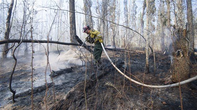 Un pompier lutte contre un feu de forêt près de Fort McMurray