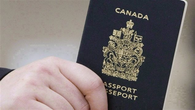 A passenger holds a Canadian passport before boarding a flight in Ottawa on Jan 23, 2007.
