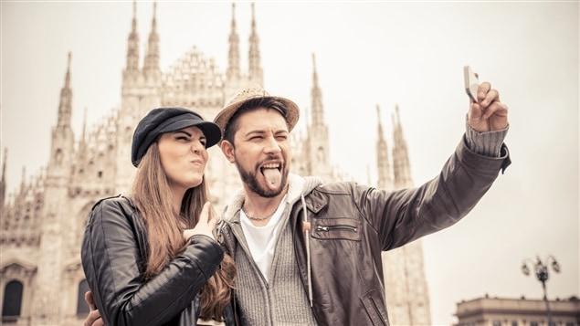 Des touristes se prennent en photo devant le Dôme de Milan.