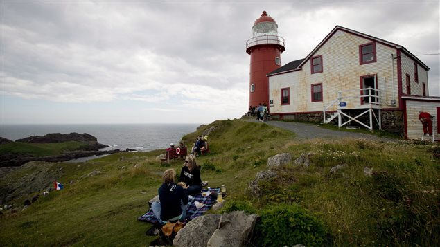 Picnickers take in the view as they sit on the grass outside the Ferryland lighthouse in Ferryland, N.L., Thursday, August, 8, 2013.