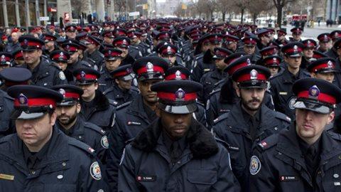 Des policiers de Toronto avec des agents noirs à l'avant plan. (Chris Young/Canadian Press)