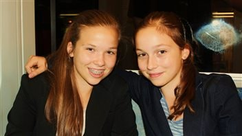 Emma, right, and Julia Mogus in 2012 when they created 'Books With No Bounds.' Emma has her right arm around her. Both have gorgeous, freshly washed long, light brown hair. Both are wearing dark sports jackets. Julia smiles through a full set of braces.