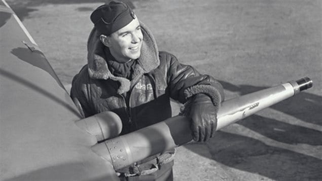 Flight Lt Charley Fox leaning on the wing of his Spitfire with its 20mm cannon