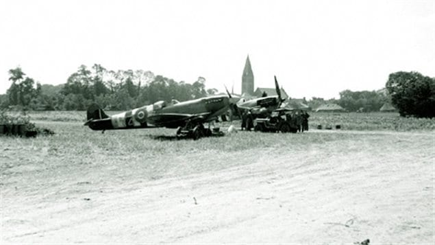 RCAF 412 Squadron Spitfires at their base in Beny-sur-Mer operating from a makeshift dir airstrip. Note the D-Day paint scheme -black and white stripes on the planes. The lead plane is a MkIX with 4-blade prop and 20mm wing cannon.