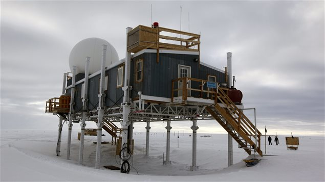 In this Friday, July 15, 2011 photo, scientists walk on the snow surrounding Summit Station, a small research facility situated 10,500 feet above sea level, on top of the Greenland ice sheet.