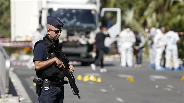 Un policier monte la garde alors que l'enquête se poursuit autour du camion qui a foncé dans la foule rassemblée sur la promenade des Anglais, à Nice, lors de la fête nationale.