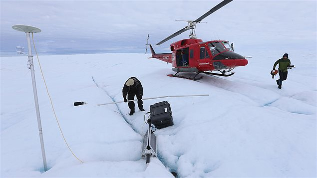 David Shean a Ph.D. student at the University of Washington (R) and Scientist Ian Joughin of the University of Washington place a GPS system into the ice on July 17, 2013 on the Glacial Ice Sheet, Greenland.