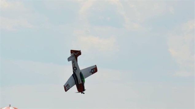 Bruce Evans flying in the Cold Lake Air Show just before crashing Sunday afternoon. We see (from a good distance from the ground) a black and silver single engine plane heading straight down toward the ground.