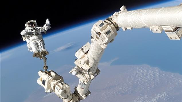 Un astronaute arrimé au Canadarm, le « bras spatial canadien » attaché à une navette spatiale américaine
