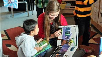 "In 2012, Emma and her older sister, Julia, co-founded ""Books With No Bounds."" They have since shipped 115,000 books to communities across Canada and around the world, impacting the lives of 150,000 world-wide. We see Emma dressed in a red sweater reading a large picture book with a child who appears to be about five. The child appears madly in love with Emma."