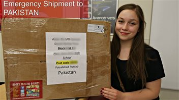 Emma Mogus prepares a shipment of books bound for Pakistan. Se see her in a dark dress and a somewhat shy smile holding a giant paper-wrapped package.At the top in red are the words,