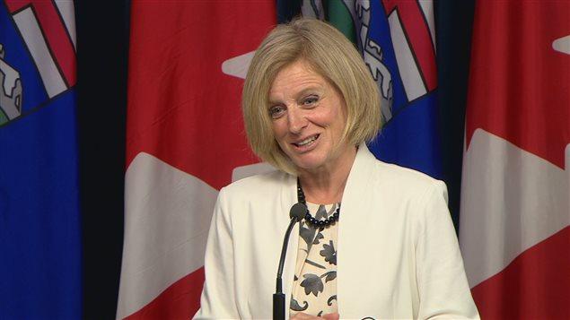 Rachel Notley devant des drapeaux du Canada et de l'Alberta