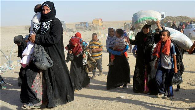 Des gens fuyant la violence perpétrée par le groupe armé État islamique arrivent à la base militaire de Ramadi en Irak le 27 juin 2016.