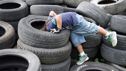 Skill testing question: What is this kid looking for? We see a pre-teen kid wearing jeans that stop at the knee and a blue tee shit. His head is buried in the hole of a top tire of a pile of tires at a dump filled with more tires.