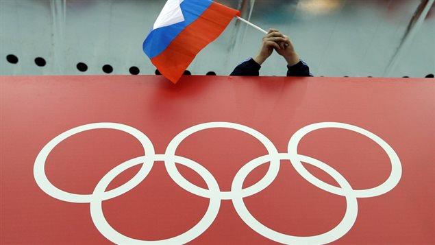 Un spectateur agite un drapeau russe au-dessus des anneaux olympiques lors des Jeux olympiques de Sotchi.