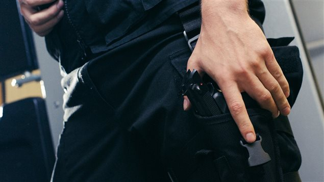 Un policier tient un pistolet.