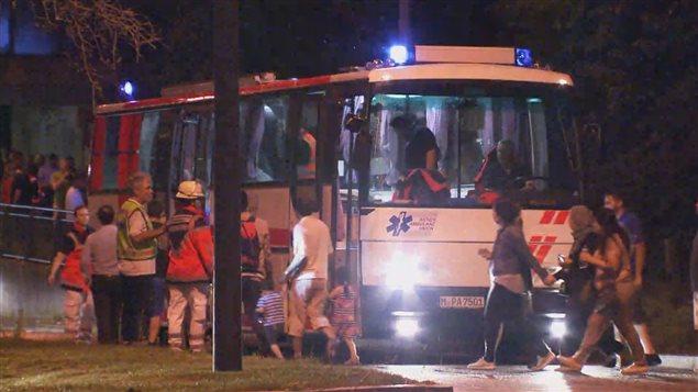 Des personnes ayant fui le centre commercial Olympia sont dirig�es vers des autobus sp�ciaux par les �quipes de secours.