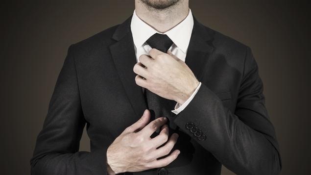 Un homme ajuste son nœud de cravate.