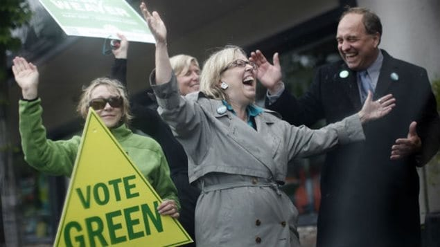 "Federal Green Party Leader Elizabeth May (seen campaigning in Victoria in 2013) had high hopes of winning the riding in last fall's federal election. It didn't happen and now the party has been sanctioned for contravening the Canada Election Act. We see May in the midst of supporters wearing a grey raincoat. Her arms are extended wide and her mouth agape as she embraces a crowd. Behind her stands blond lady holding a sign that says ""Vote Green."""